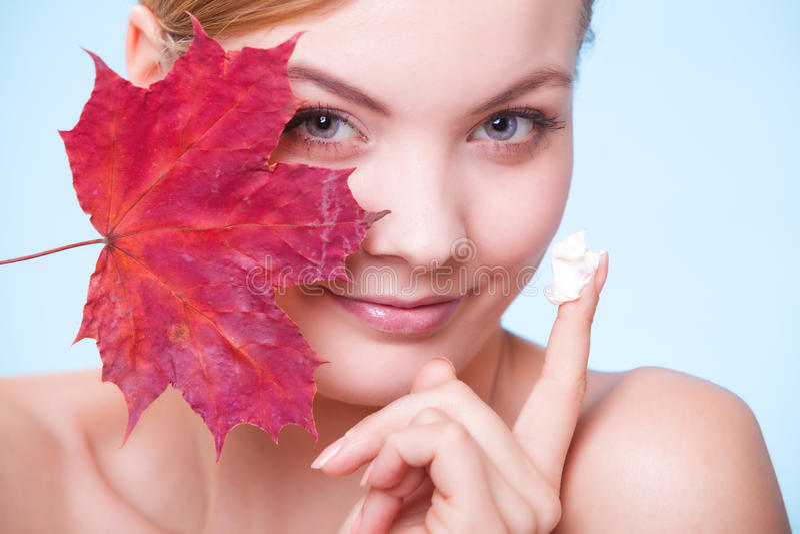 护肤。有红色叶子和奶油的妇女女孩 库存照片
