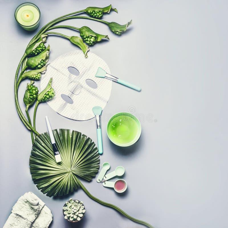 护肤化妆用品和面部板料面具 与热带叶子和花的各种各样的血清、奶油和胶凝体化妆用品产品 免版税库存照片