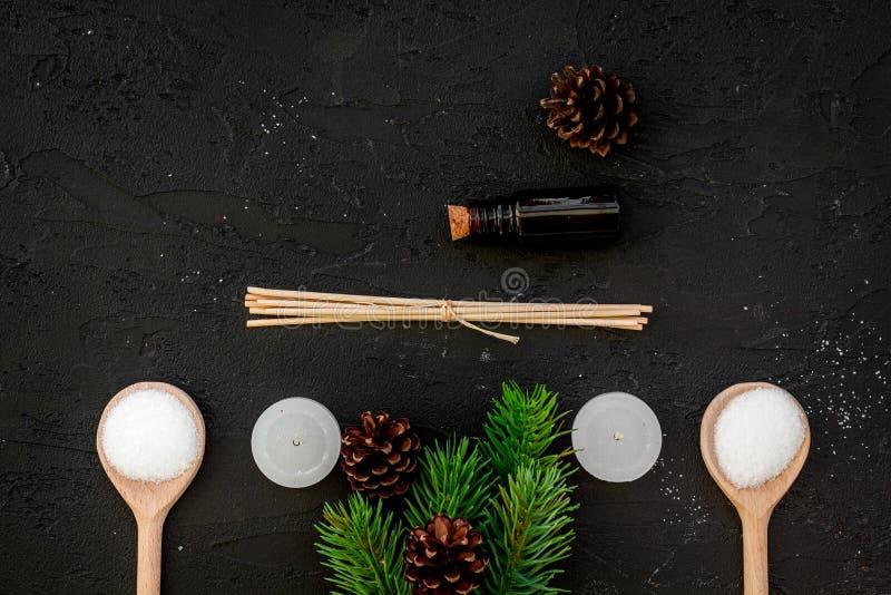 护肤和放松 化妆用品和芳香疗法概念 杉木温泉盐、油、云杉的分支和pinecones在黑色 免版税库存照片