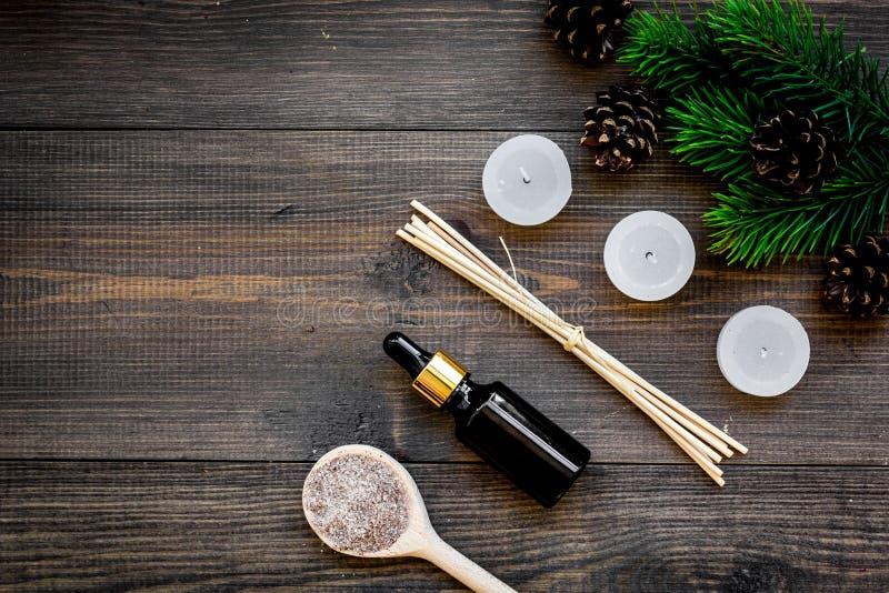 护肤和放松 化妆用品和芳香疗法概念 杉木温泉盐和油在黑暗的木背景顶视图 免版税库存照片