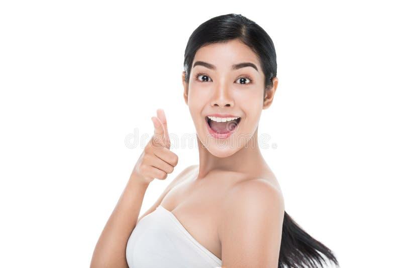 护肤把手指指向的秀丽妇女快乐的照相机微笑和 与裁减路线的亚洲女性秀丽模型 免版税库存图片