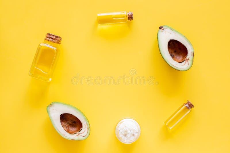 护肤的化妆用品 在一半的鲕梨油在黄色背景顶视图拷贝空间的鲕梨附近 库存图片