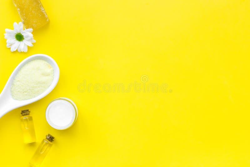 护肤的自然有机温泉化妆用品与春黄菊 温泉盐,奶油,肥皂,在黄色背景顶视图的油 免版税库存照片