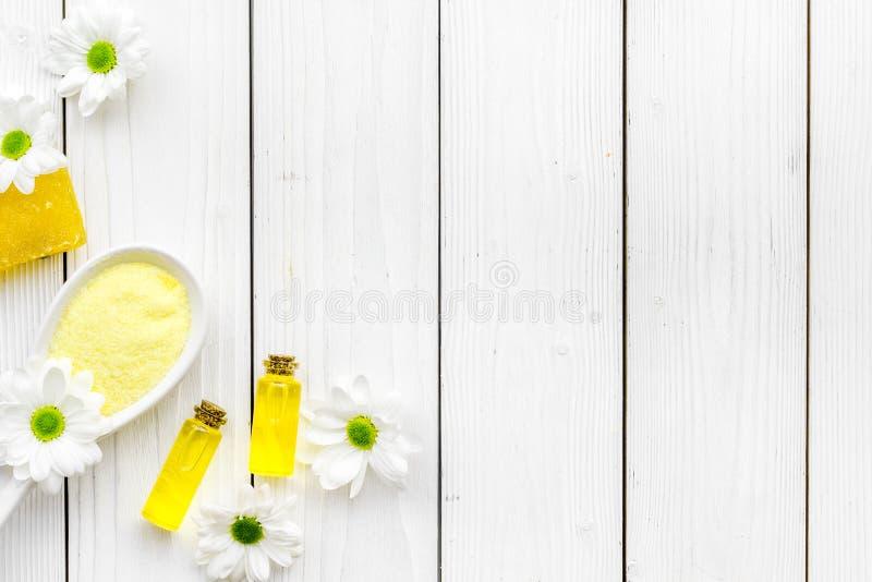 护肤的自然有机温泉化妆用品与春黄菊 温泉盐,油,在白色木背景顶视图拷贝的肥皂 免版税库存图片