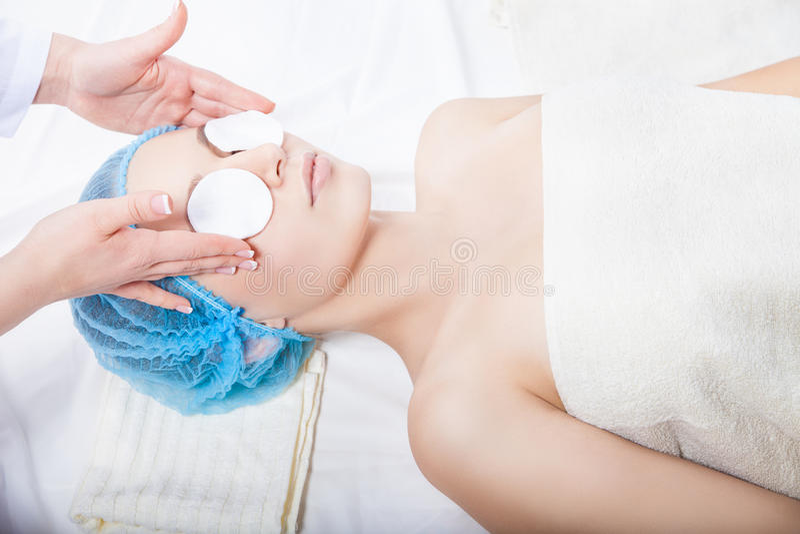 护肤-妇女由美容师的清洁面孔 免版税库存图片