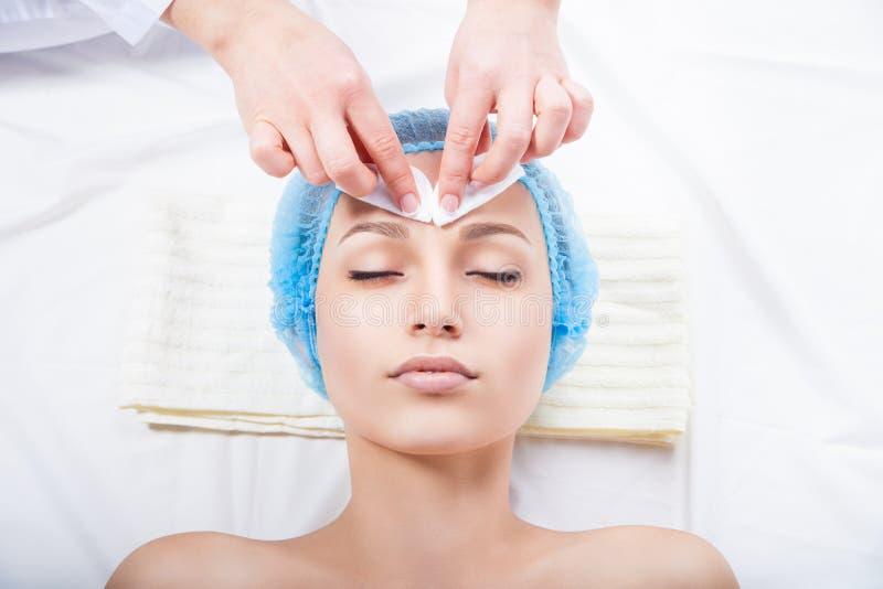 护肤-妇女由美容师的清洁面孔 库存照片