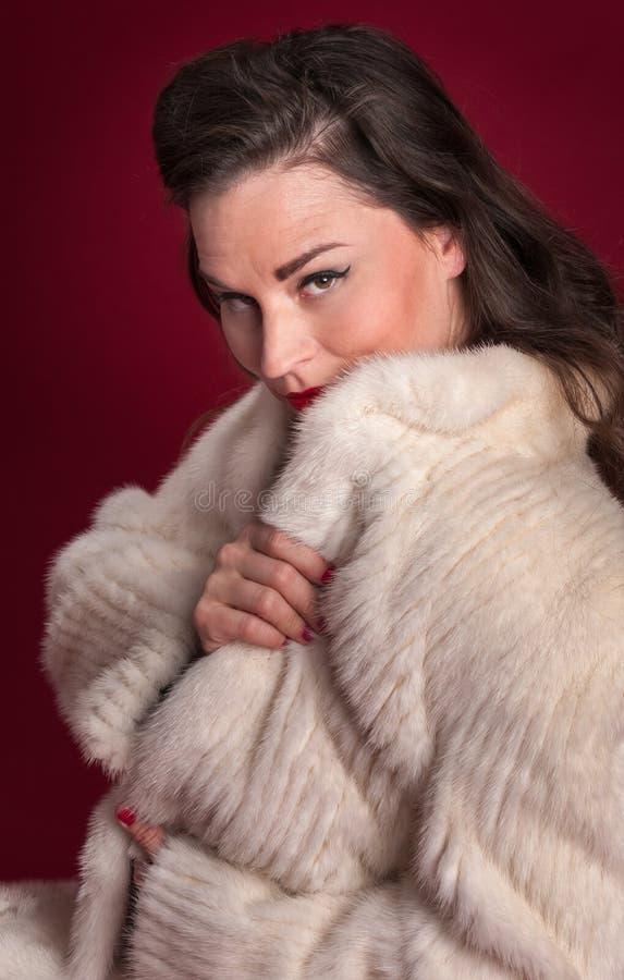 画报在白色皮大衣衣领的女孩同辈  库存图片