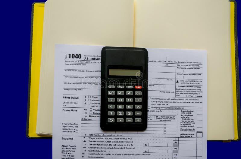 报税表1040,计算器,在蓝色背景的笔记薄 免版税库存照片