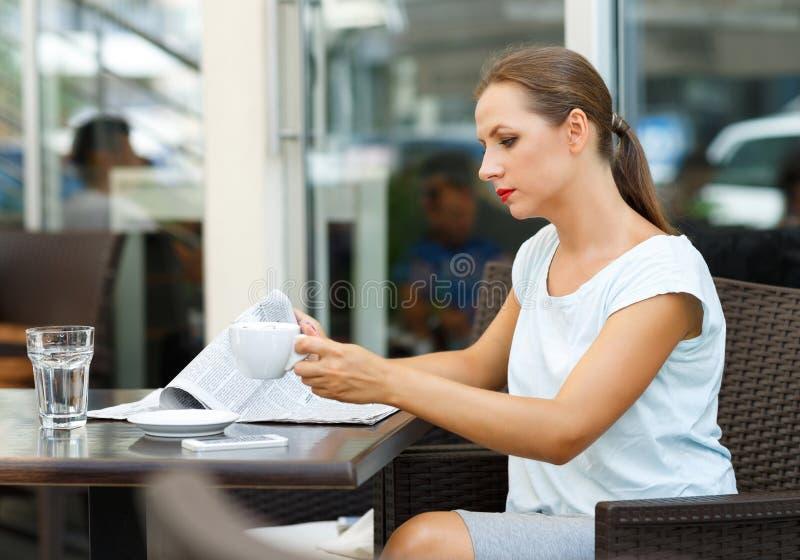 读报纸和喝早晨咖啡的可爱的妇女 库存图片