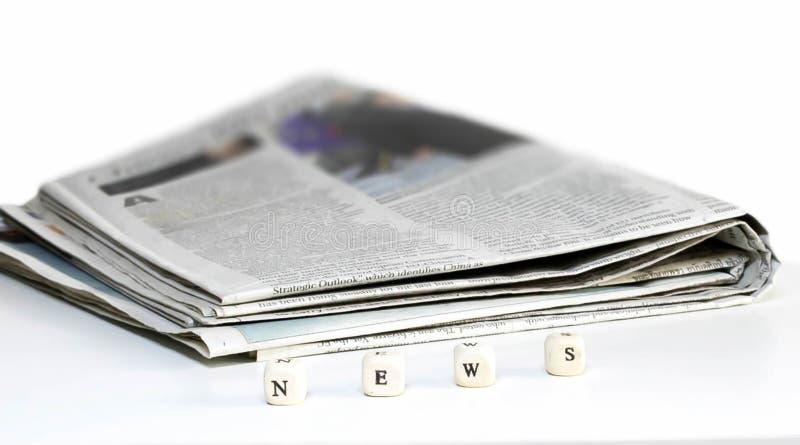 报纸折叠与在白色背景的木abc文本 库存图片