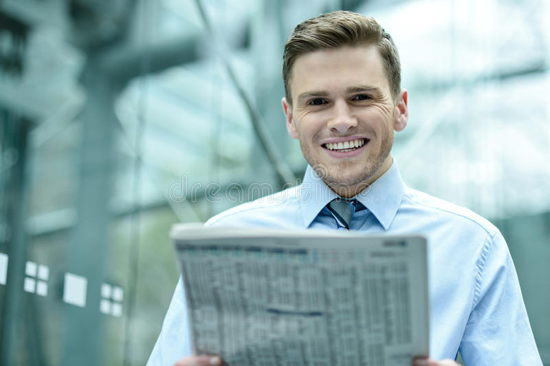 读报纸的英俊的商人 免版税库存照片