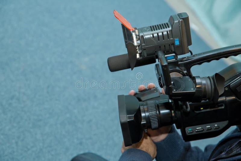 报道事件用一台摄象机 Videographer采取有赠送阅本空间的摄像头文本的 摄像头操作员 库存照片