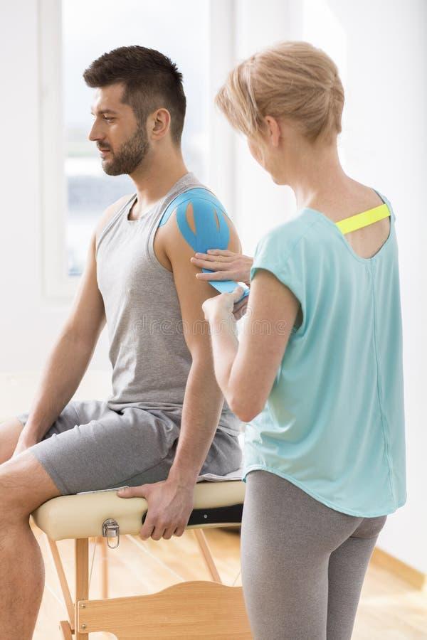 报道年轻人的身体的选择的片段的生理治疗师用特别结构补丁在kinesiotaping的疗法期间 库存照片