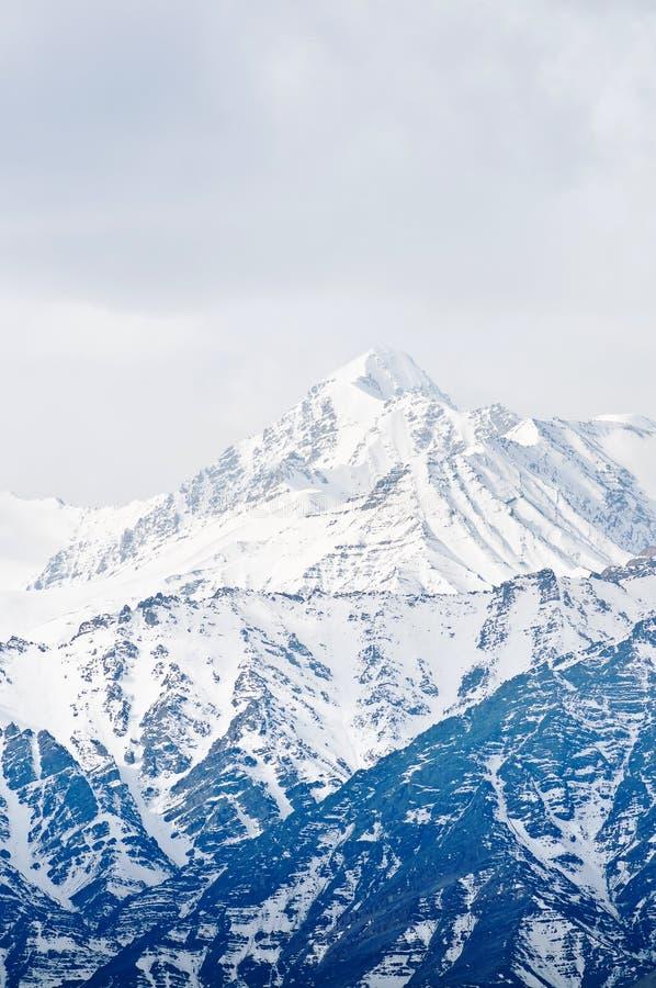 报道的高山雪顶层 图库摄影
