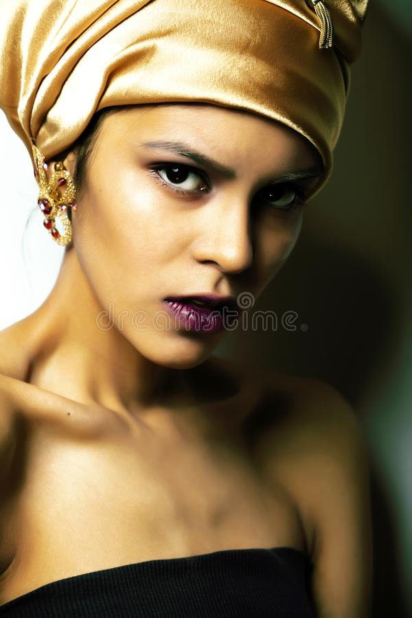 披肩的秀丽非洲妇女在头,非常与金首饰关闭的典雅的神色混血儿构成 库存照片