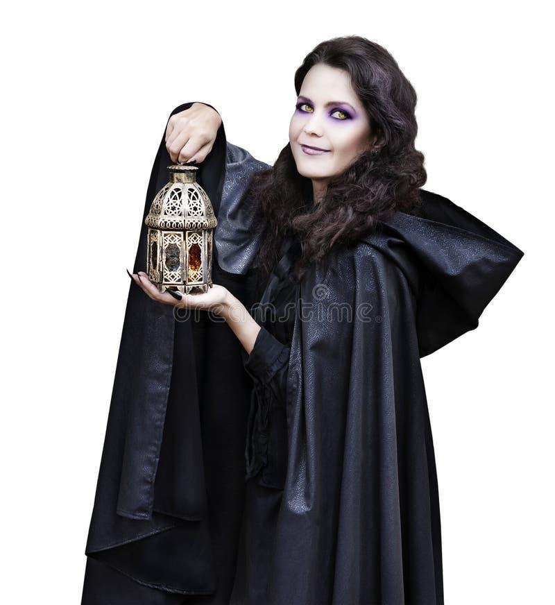 披风的美丽的巫婆与蜡烛的灯笼 免版税库存图片