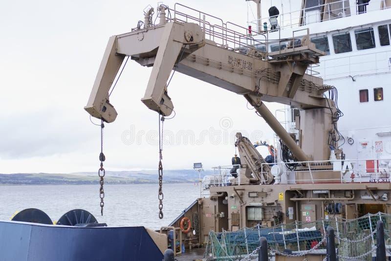 抬头在大船举的货物对在小船的运输 免版税库存图片