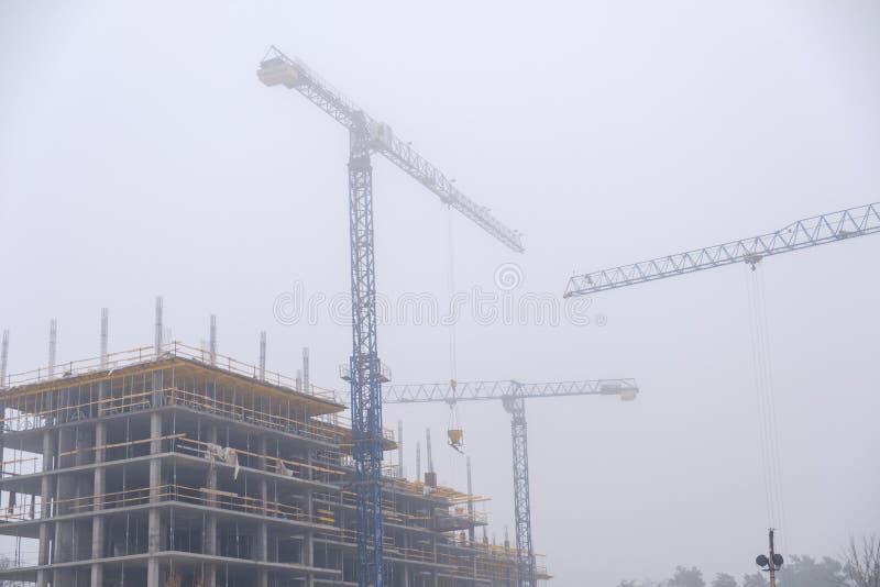 抬头在建设中摩天大楼背景一场雾的在被放弃的  图库摄影