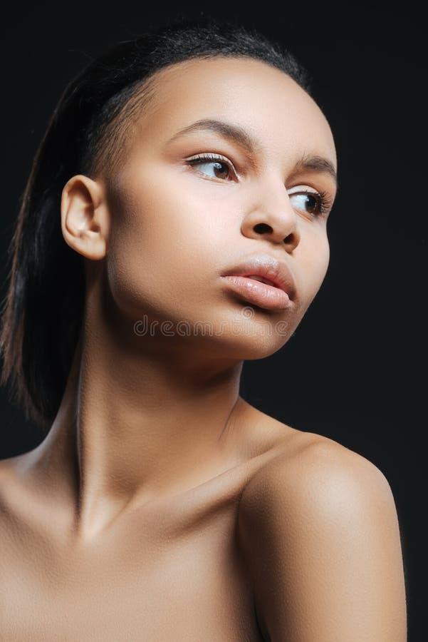 抬头她的脖子的逗人喜爱的好妇女 免版税库存图片