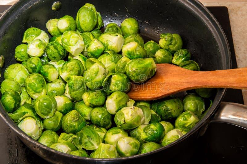 抱子甘蓝小嫩卷心菜搅动与在煎锅的一把小铲 厨房顶面板材和火炉在 库存照片