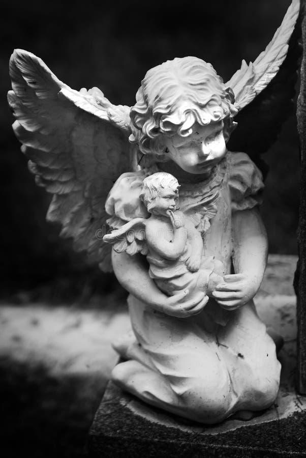 抱孩子的小天使雕象飞过宗教 免版税库存照片