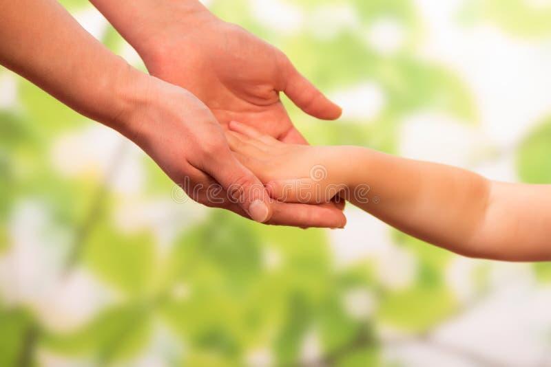抱孩子的男性手 免版税库存照片