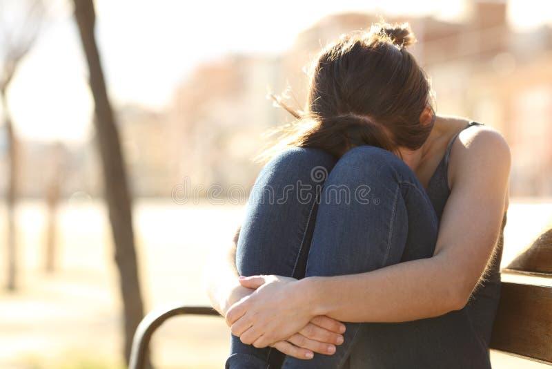 抱怨在一条长凳的哀伤的妇女在公园 免版税库存照片