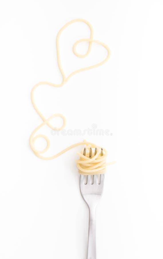 抱怨在叉子的煮熟的意粉面团与心脏形状,在白色背景 免版税库存图片