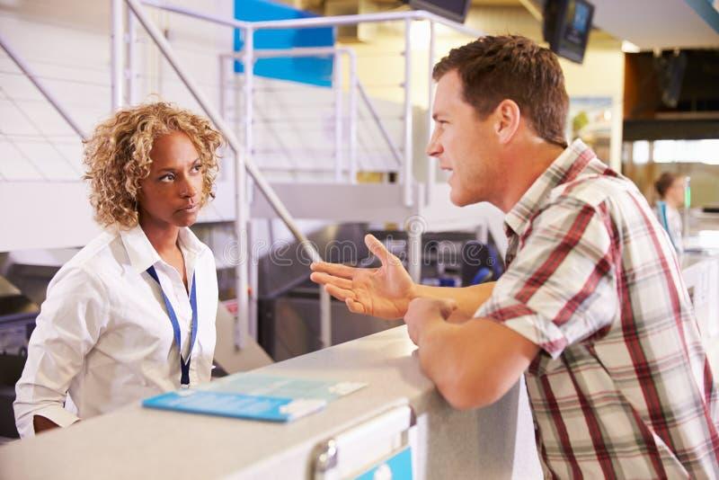 抱怨对职员的恼怒的乘客在机场登记 免版税库存图片