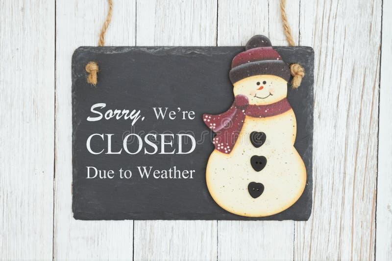 抱歉我们被关闭得到期风化在一个垂悬的黑板的标志有雪人的 库存图片