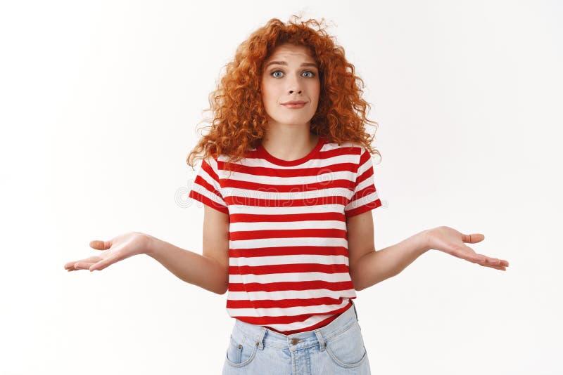 抱歉没有的想法 为难的笨拙耸肩手的红头发人卷曲妇女夏天镶边T恤杉斜向一边缩拢嘴唇 图库摄影