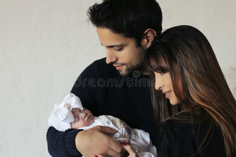 抱着一个小婴孩的年轻父母新出生 免版税库存照片