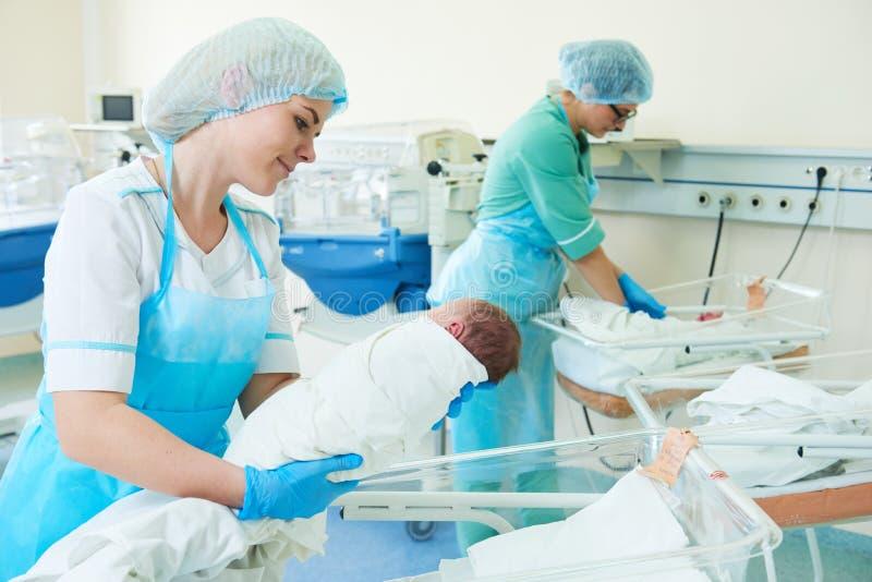 抱着一个新出生的婴孩的年轻女性护士在医院 免版税库存图片