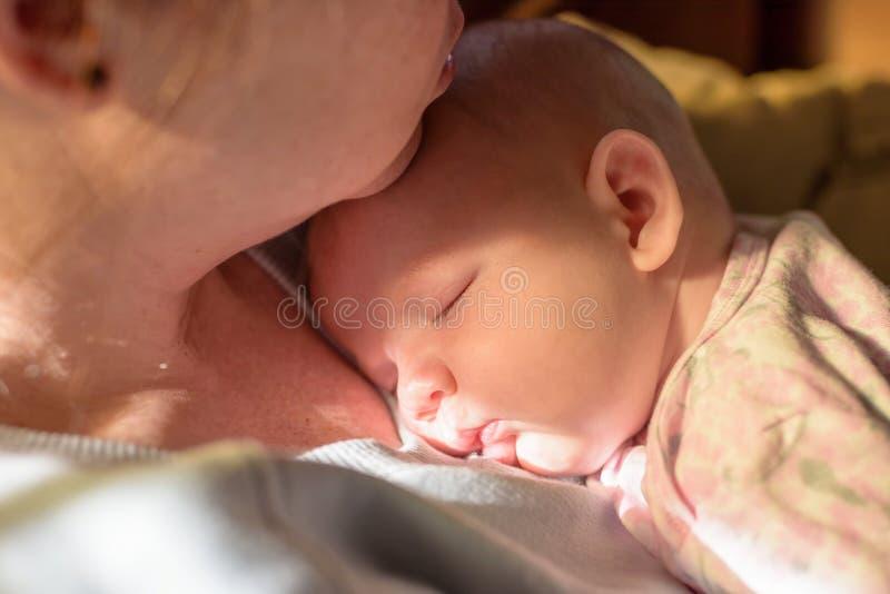 抱着一个睡觉的新出生的婴孩的妇女的特写镜头在早期的早晨 库存图片
