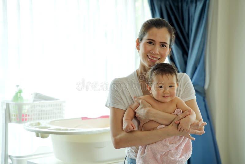 抱着一点可爱宝贝的亚裔美丽的母亲在洗浴以后 库存照片