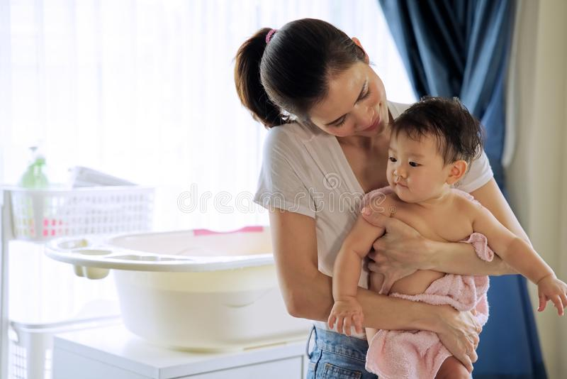 抱着一点可爱宝贝的亚裔美丽的母亲在洗浴和看和她的儿童身分以后在屋子里 浴缸和 库存照片