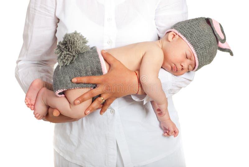 抱着兔宝宝服装的母亲睡觉的婴孩 图库摄影