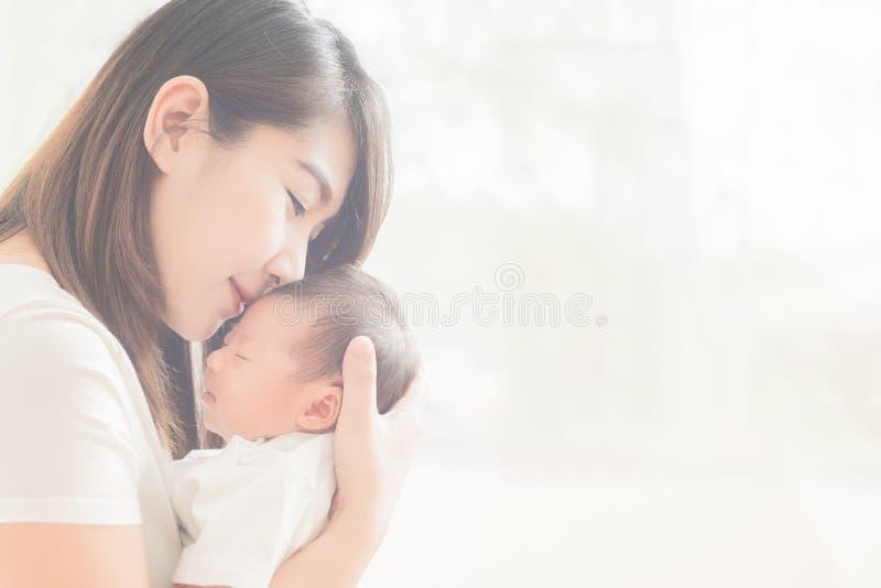抱着可爱的儿童婴孩的愉快的母亲 库存图片