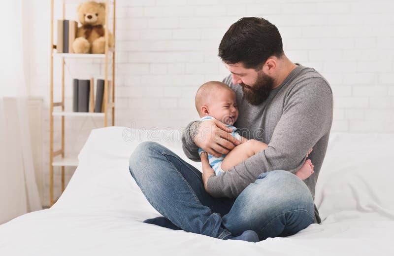抱着哭泣的困逗人喜爱的新生儿的年轻父亲 免版税库存照片