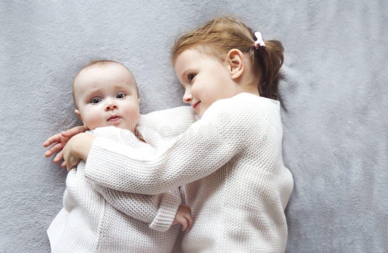 抱着在床上的逗人喜爱的白种人女孩姐妹生活方式画象一点婴孩 免版税库存照片