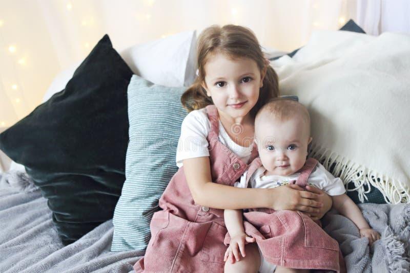 抱着在床上的逗人喜爱的白种人女孩姐妹生活方式画象一点婴孩 库存图片