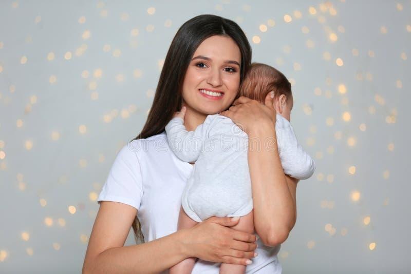抱着她可爱的婴孩的年轻母亲 免版税图库摄影