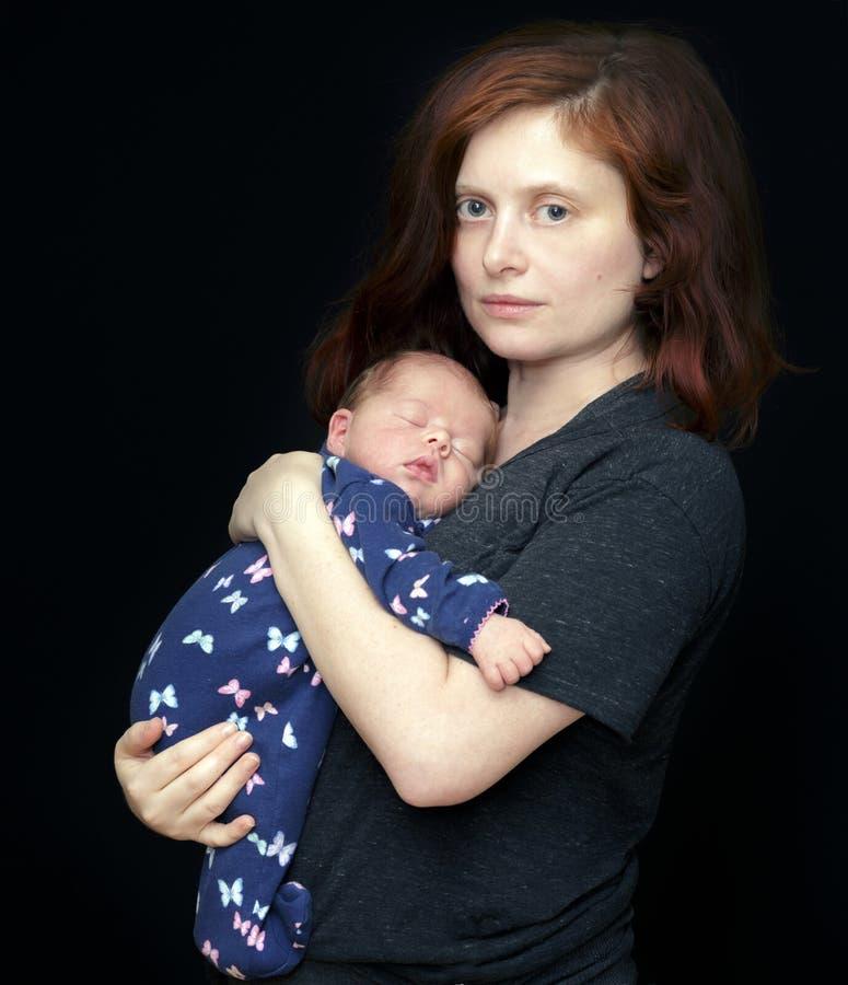 抱着她新出生的婴孩的母亲 免版税库存照片