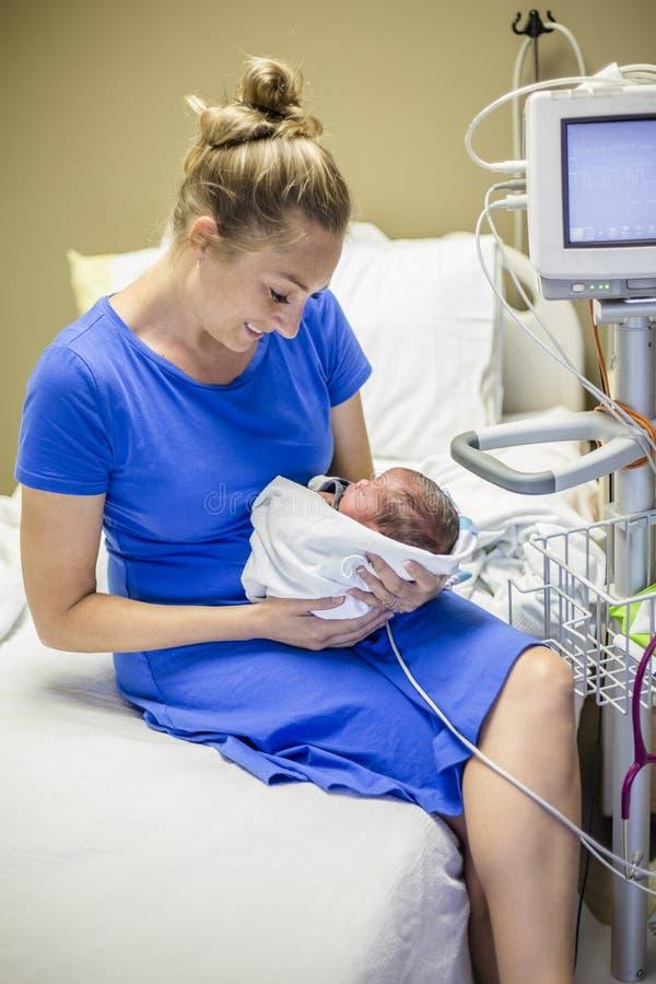 抱着她新出生的早产儿的微笑的母亲在医院 图库摄影