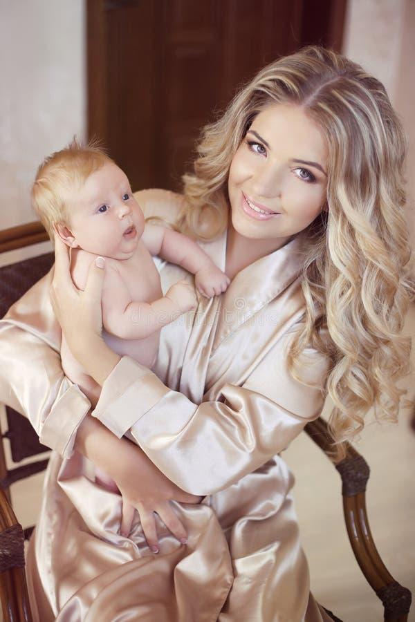 抱着她新出生的婴孩的愉快的母亲 使用与新出生的妈妈 库存照片