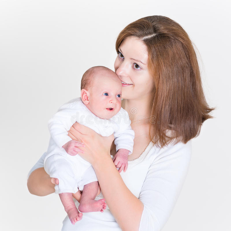 抱着她新出生的婴孩的愉快的年轻母亲 免版税图库摄影