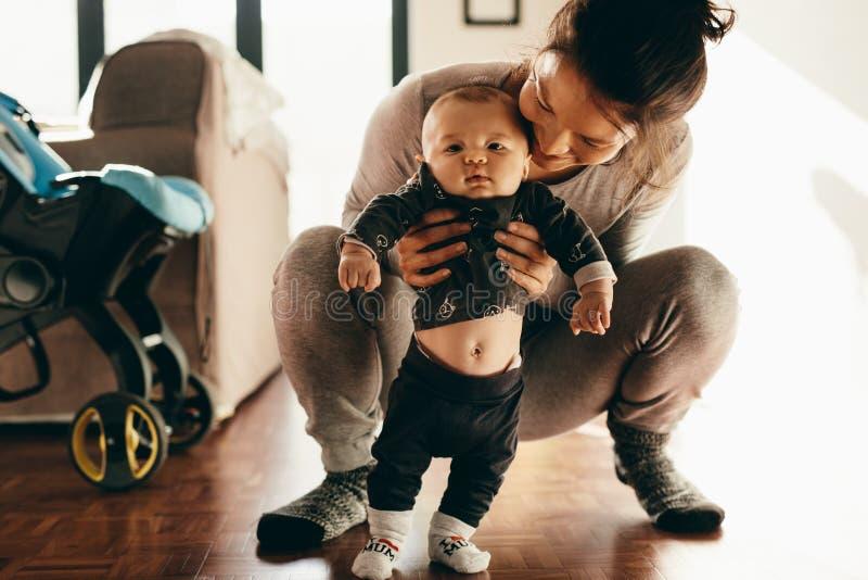 抱着她的婴孩的妇女蹲在地板上 库存照片
