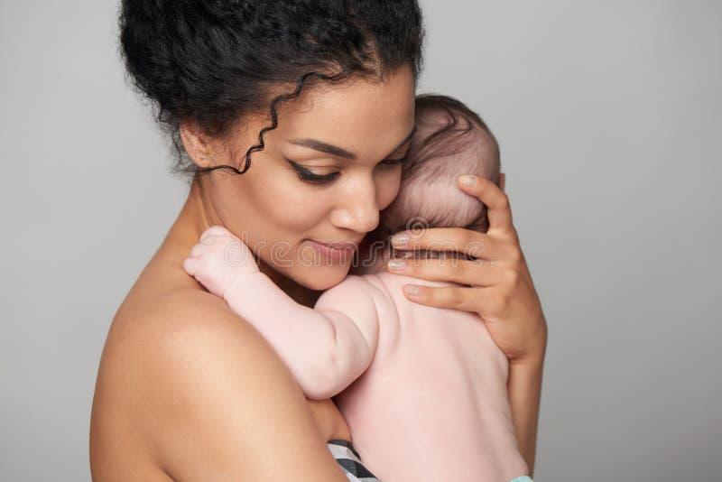 抱着她的胳膊的俏丽的妇女一个婴孩 免版税库存图片