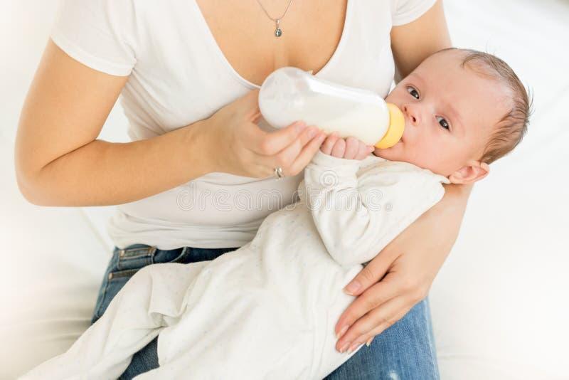 抱着她的婴孩和哺养与米尔的母亲特写镜头画象 库存图片