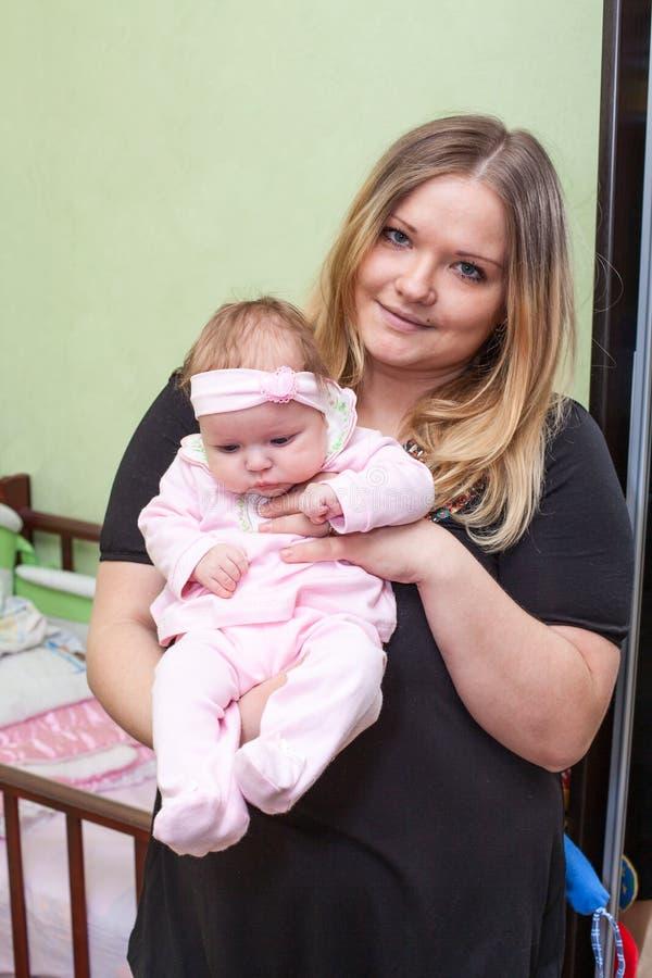 抱着她的婴孩的爱恋的年轻母亲 免版税库存照片